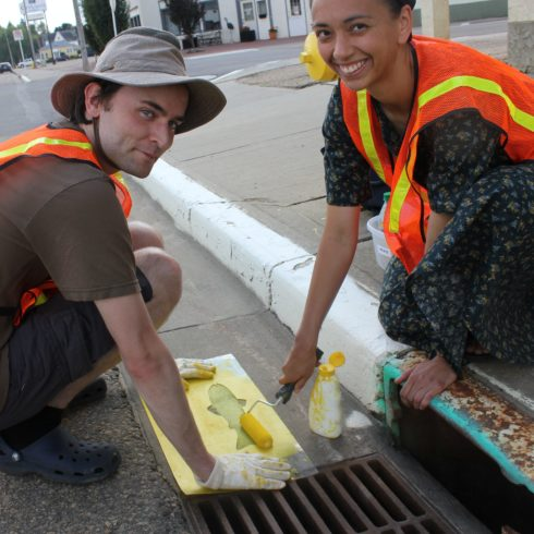 Two volunteers kneel beside a storm drain where they use a stencil to paint a yellow fish