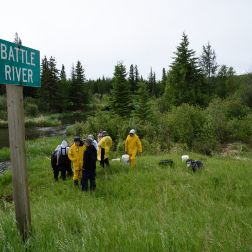 A class stand down at the river on their field trip. A Battle River Sign is in the foreground