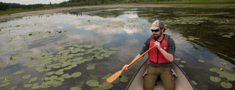 A man paddles a canoe on the still waters of Battle Lake