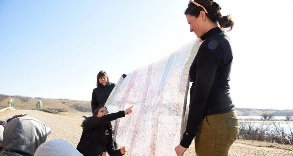 BRWA staff hold a map to show a group of students the Battle River Watershed