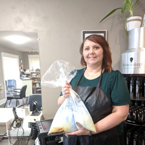 Salon Owner holds bag of chemical waste