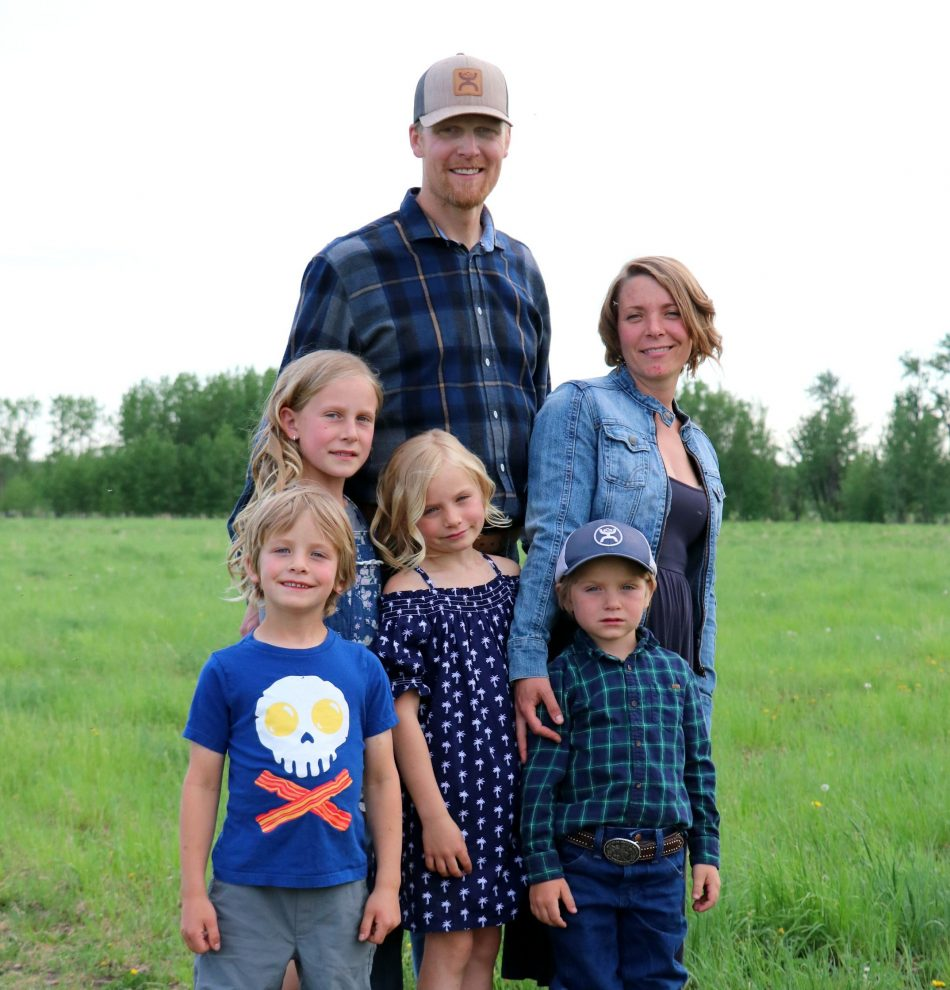 The Schamber family (parents and 4 children) group together on their farm.